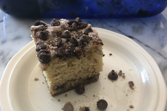 Slice of chocolate chip cake covered in cinnamon, sugar and chocolate chips