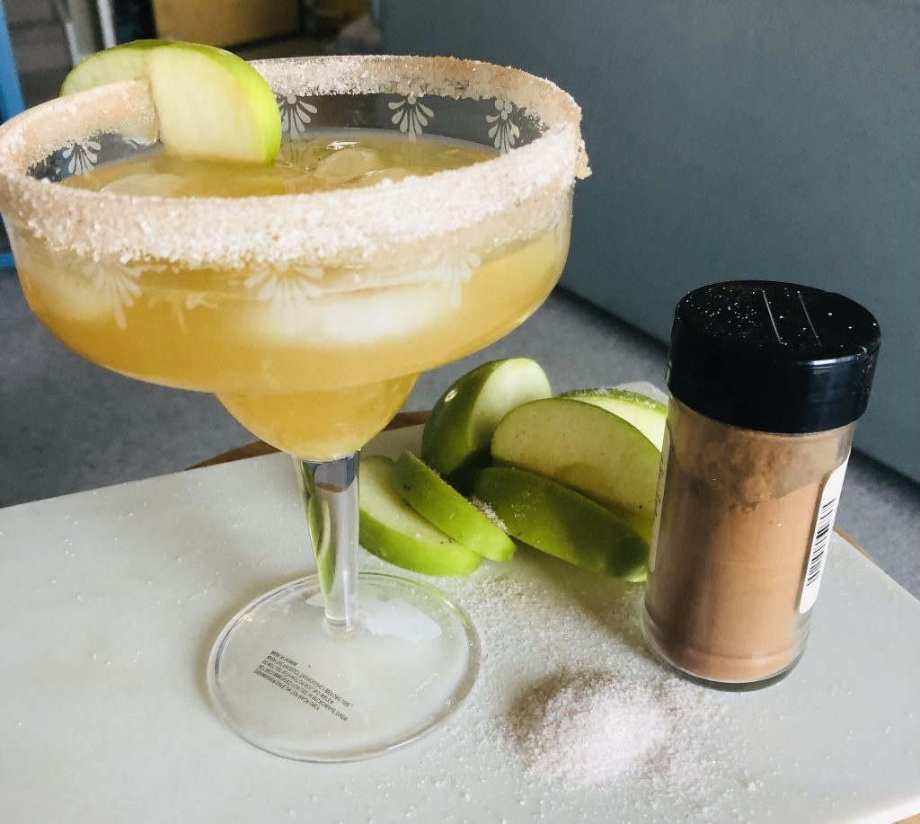 Apple cider pear margarita on the rocks in a glass rimmed with cinnamon nutmeg sugar mixture and garnished with apple slices.