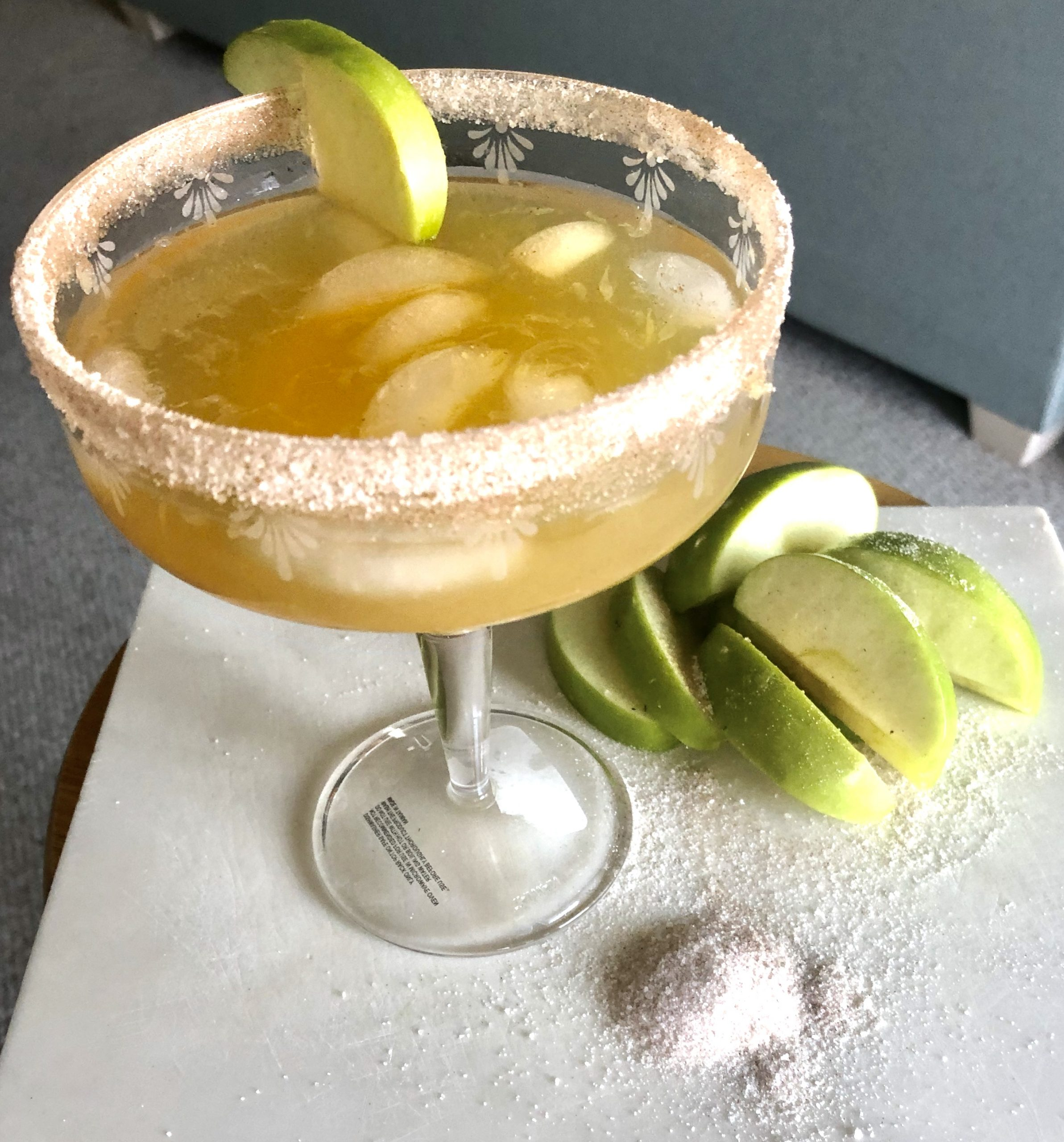 Apple Cider Pear Margarita in a glass rimmed with cinnamon nutmeg sugar and garnished with granny smith apple slices